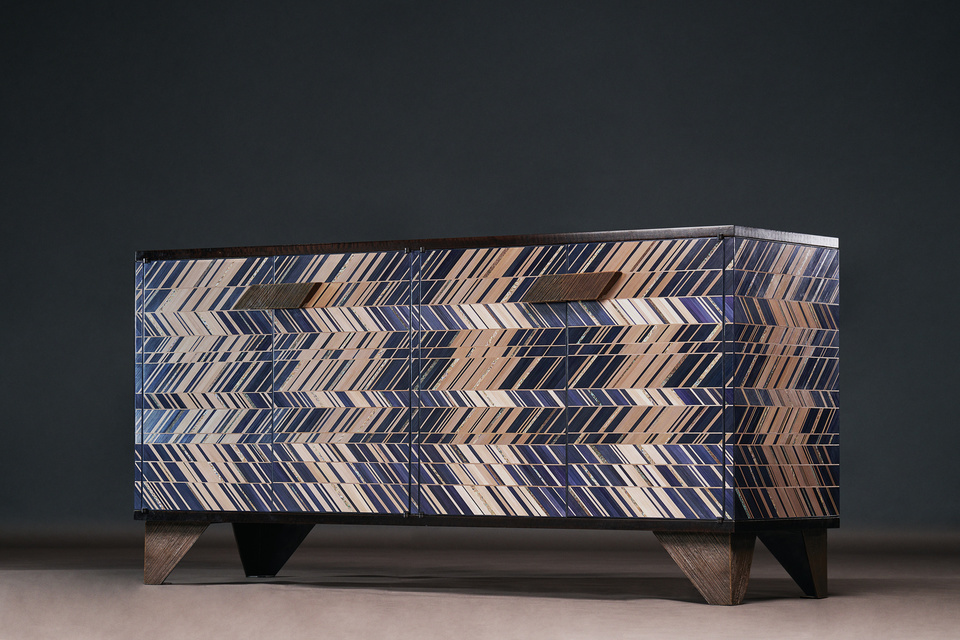Prism Sideboard FG003677 Intarsia A serious yet delightful credenza that blends a myriad of materials into a functional and elegant whole. Both light and dark, raw and refined, this piece dazzles gently. Mother-of-pearl, patinated copper, lustrous indigo and taupe straw marquetry inlaid by hand over the front and sides of the cabinet. Custom made feet elevate the piece and matching handles give a sensuous tactility to the touch. The top is smoked Spanish eucalyptus and the interior is figured cool maple with adjustable shelves and generous soft closing drawers.