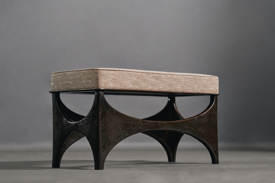 Wing Bench FG003689 Intarsia A piece of sculpture to sit upon. Distressed and generous with sinuous structural lines. A gentle lip protrudes to support the seat cushion. Hand-woven Thai silk finishes the top. The bronze-patinated surface has a gently worn finish that comes forth when observed.